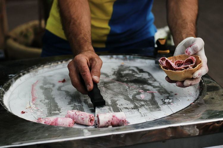 Midsection of man preparing ice cream