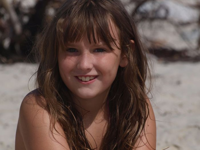 Close-up portrait of smiling teenage girl at beach
