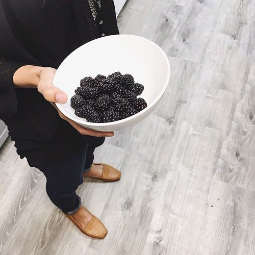 Low section of woman holding blackberries in bowl