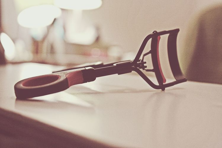 Close-up of eyelash curler on table