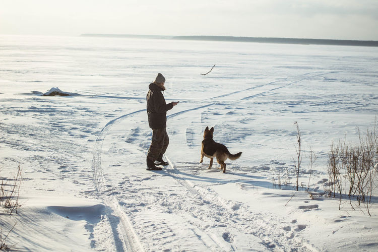 Man Playing With Dog During Winter