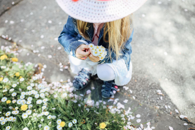 One Person Real People Flowering Plant Low Section Flower Plant Holding Day Lifestyles Nature High Angle View Casual Clothing Childhood Child Leisure Activity Selective Focus Freshness Hat Outdoors Spring Springtime Daisy Picking Flowers  Obscured Face Hands