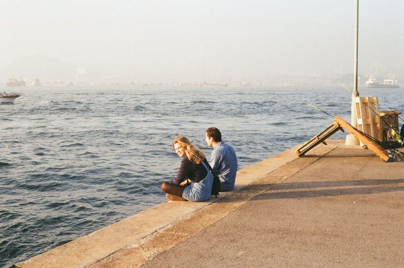 Young Couple Sitting On Pier Over Sea