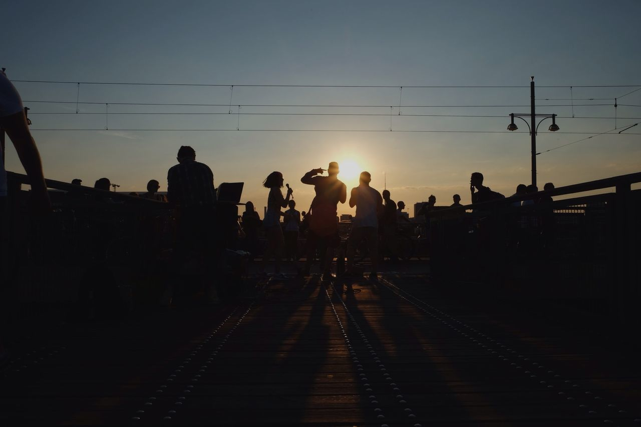 Silhouette of young woman singing on footbridge