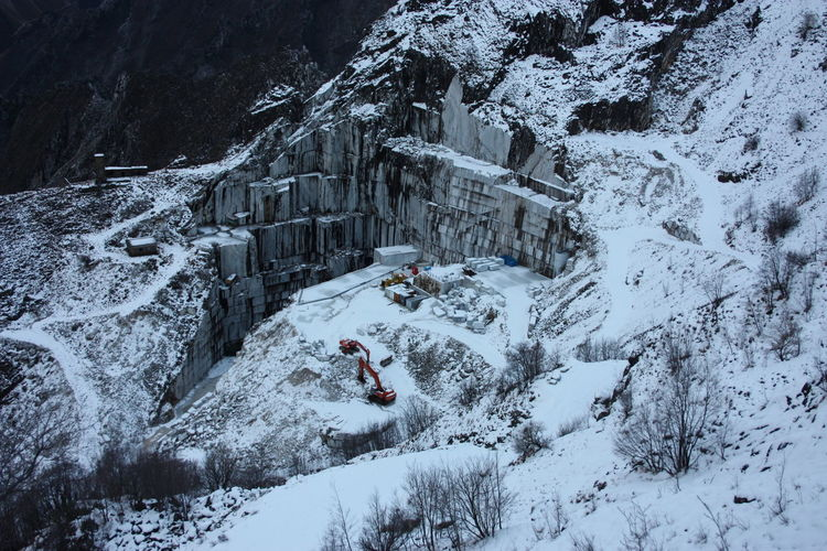 Quarries of carrara marble excavation site in mountains of apuan alps in white snow of winter
