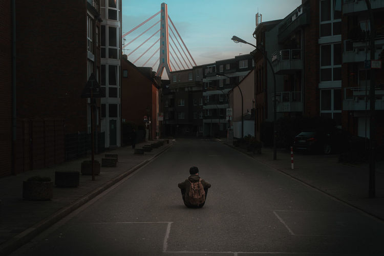 Person on road amidst buildings in city