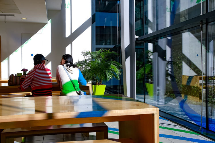 Two people at table, indoors at Salvation Army HQ cafe, central London, close to Millennium Bridge and St Paul's Cathedral. Office Salvation Army Sunlight Architecture Building Exterior Cafe Casual Clothing Day Friendship Indoors  Leisure Activity Lifestyles Men People Real People Reflections Shadow Sitting Table Togetherness Two People Water Women Young Adult Young Women