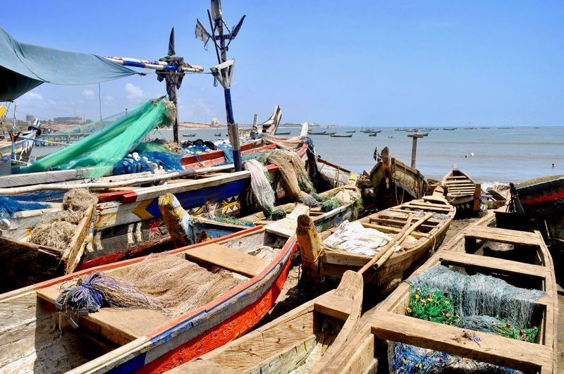 Fishing boats moored on beach against clear blue sky
