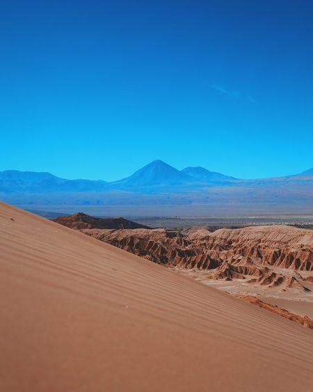 Scenic view of landscape against clear blue sky at atacama desert