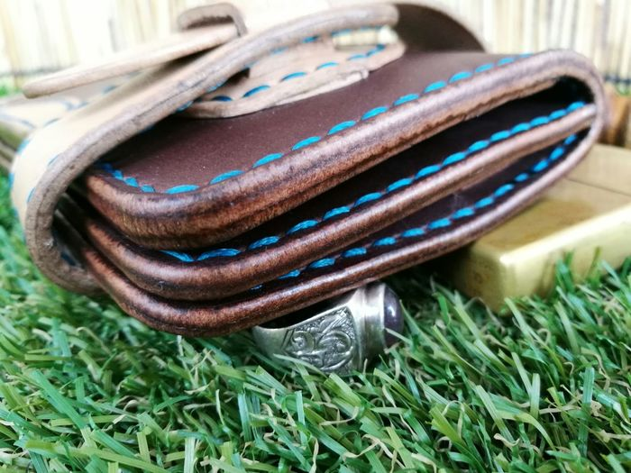 Close-up of leather wallet and ring on grass at park