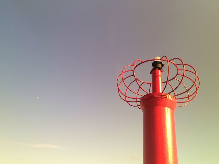Low Angle View Of Red Marker Against Sky With Distant Moon