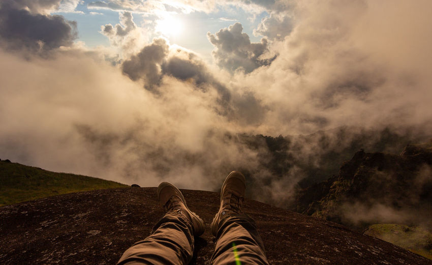 Low section of person sitting on mountain against cloudy sky during sunset