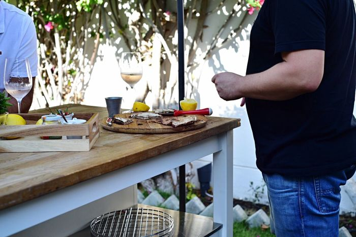 Midsection Only Men Standing Real People Adults Only Preparation  Table Food And Drink Domestic Life Men Skill  People Day Adult Dining Table Outdoors Working Dedication