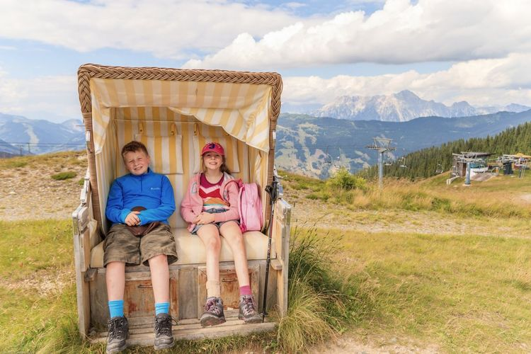 Kids resting in a fancy seat at the top of an Austrian mountain Child Females Males  Girls Family Togetherness Boys Beauty Brother Smiling Childhood Two People Happiness Vacations Cute Communication People Adventure Offspring Full Length
