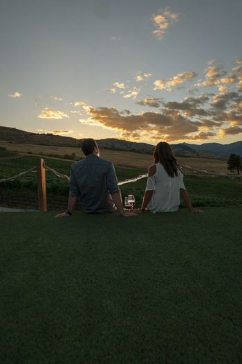 Rear view of couple sitting on land against sky during sunset