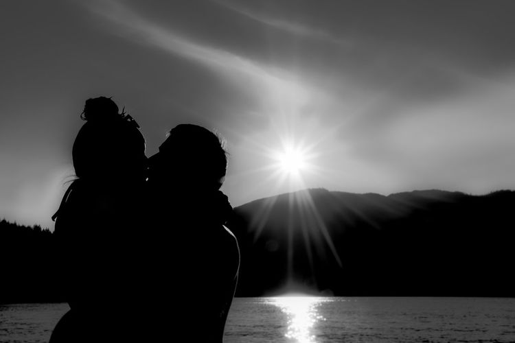 Side View Of Couple Kissing While Standing Against Sky