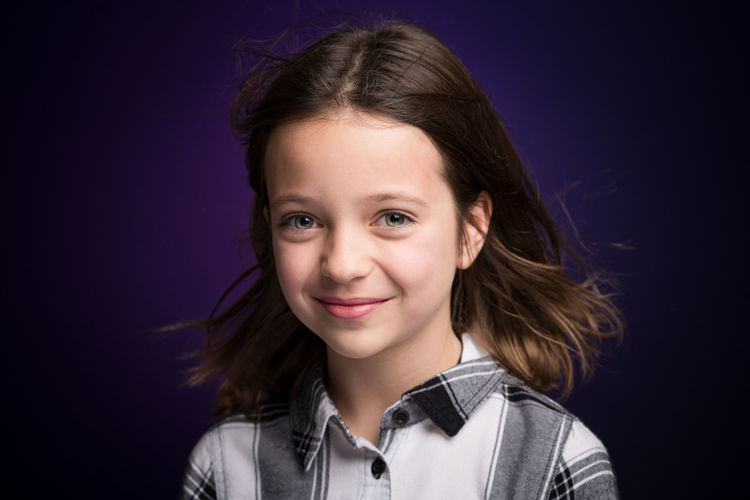 Portrait of smiling girl against purple background