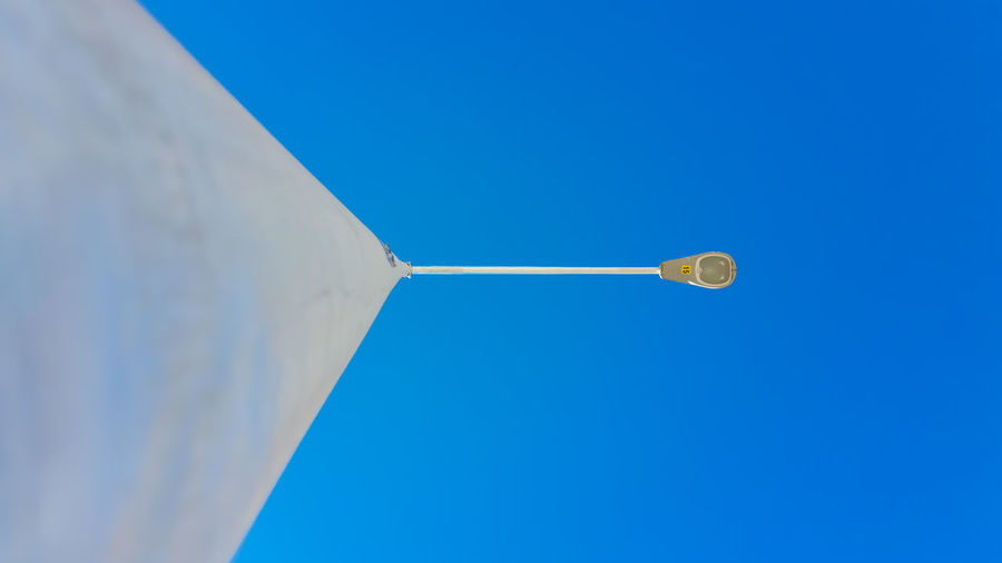 Directly below view of street light against clear blue sky