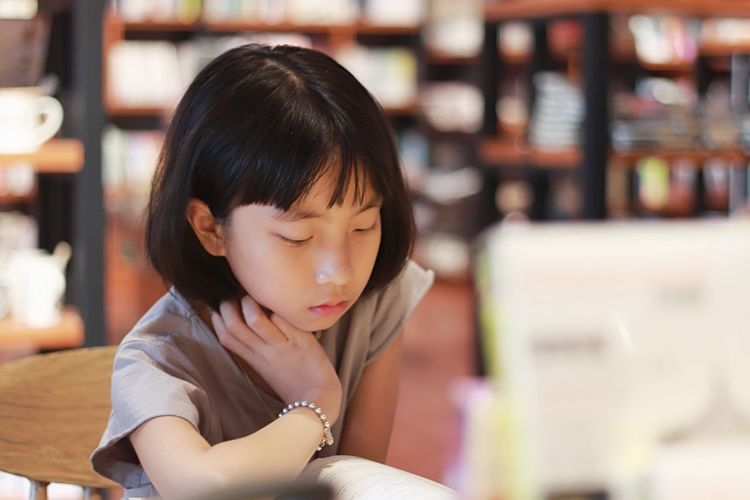 Close-Up Of Girl Reading Book In Library