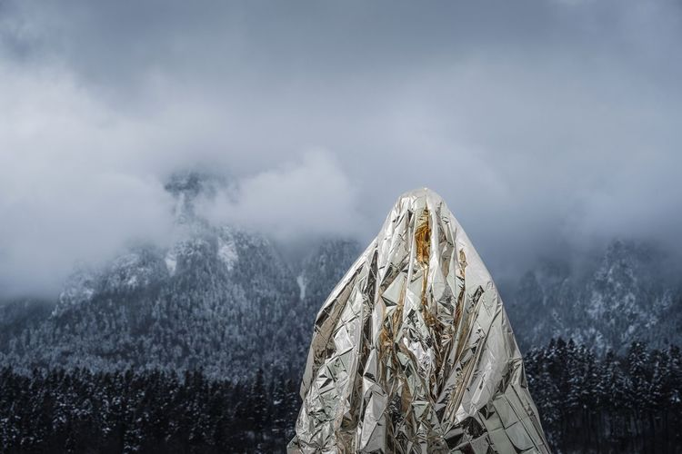 Close-up of aluminum foil against mountains during winter in foggy weather