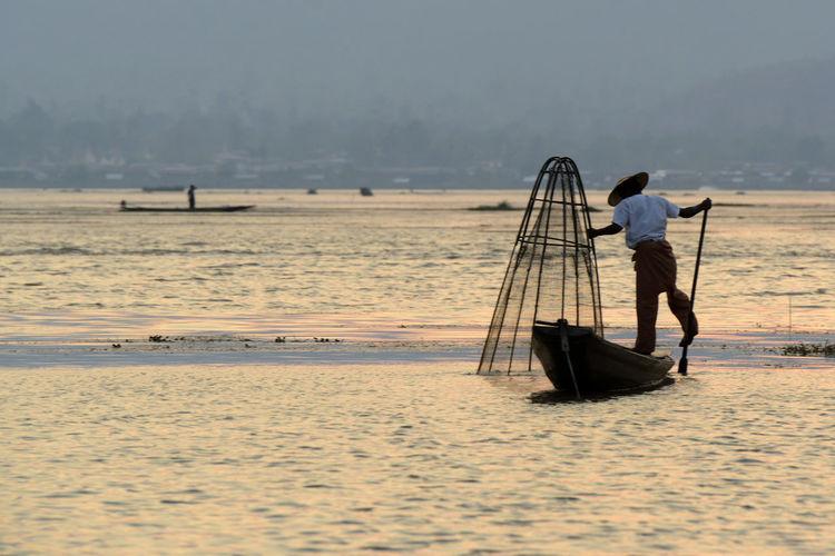 Rear view of man fishing in lake at sunset