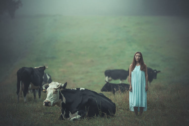 Portrait Of Woman Standing With Cows On Field During Foggy Weather