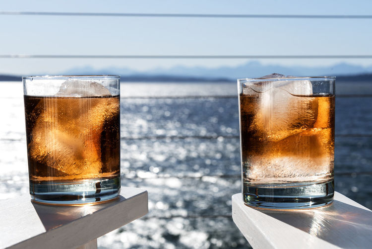 Close-up of glasses of whiskey against water