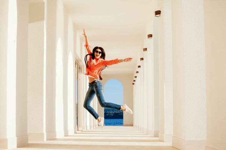 Portrait of young woman jumping in corridor