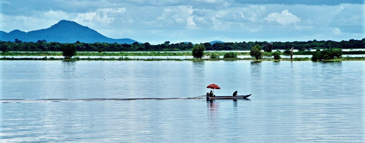 Men in boat on lake against sky