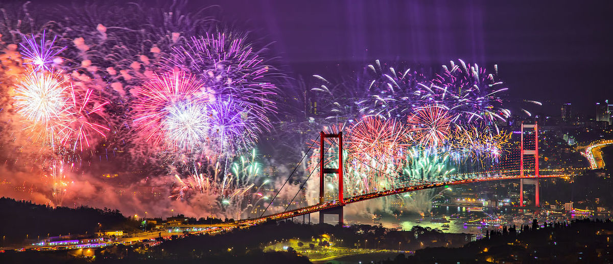 Panoramic view of illuminated bosphorus bridge with firework display at night