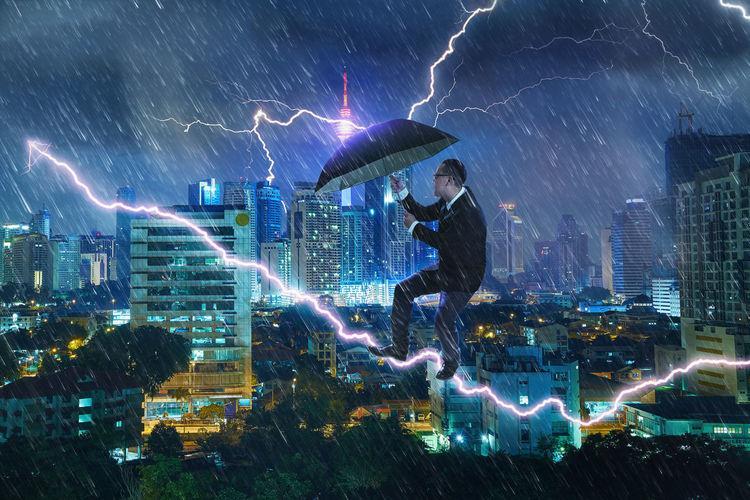Digital composite image of businessman holding umbrella while standing on thunder