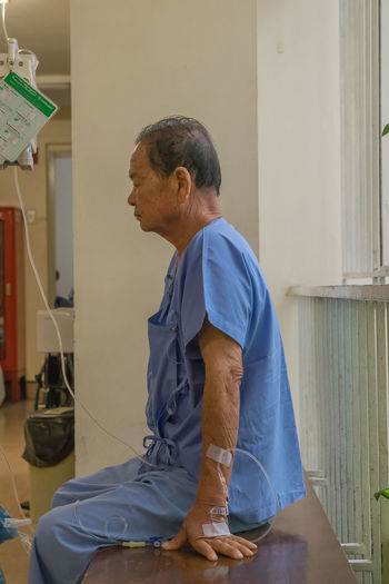 Side view of patient sitting on bench in hospital