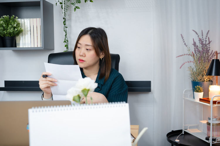 Businesswoman reading document while sitting at office
