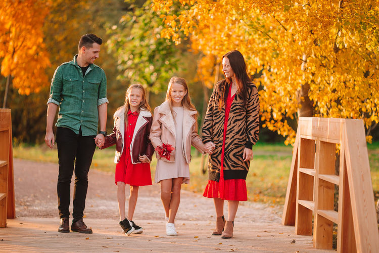 Group of people walking on autumn leaves