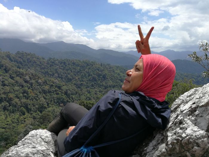 Woman gesturing peace sign while sitting on cliff against mountains