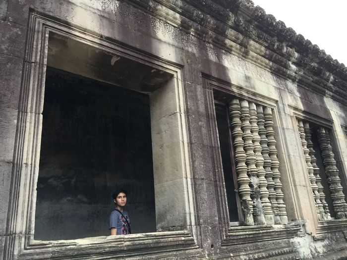 Low angle view of man standing by old building