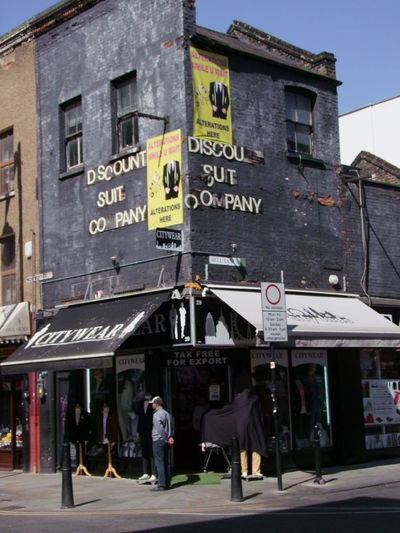Discount Suit Company Store, Wentworth Street Composition Corner Store East End London GB London Sunlight Blue Sky Building Building Exterior Capital City Clothing Shop Clothing Store Drab Colour Full Frame Incidental People Market Area Outdoor Photography Shop Store Street Text Tourist Destination Travel Destination Uk Western Script