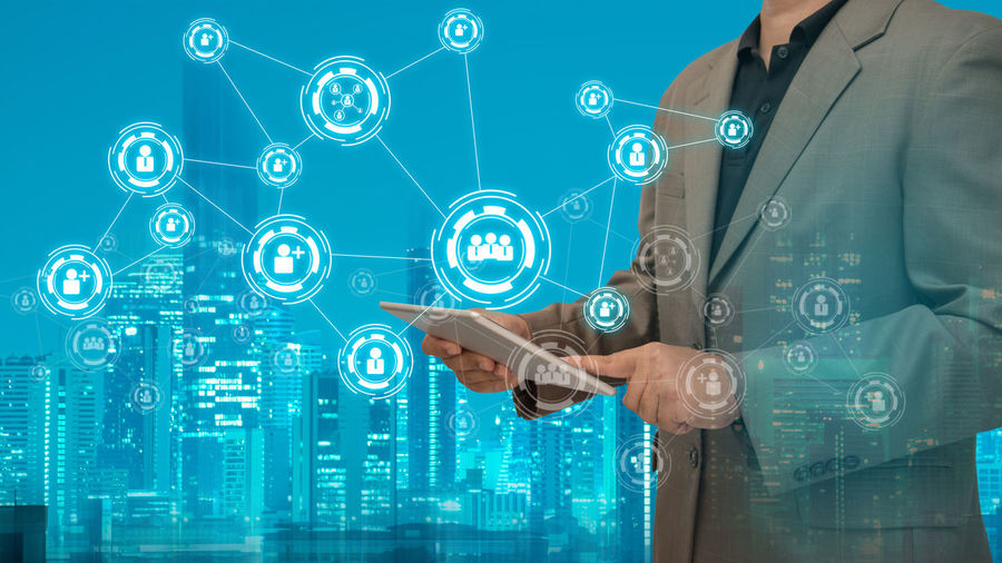 Digital composite image of businessman using digital tablet by various icons in city