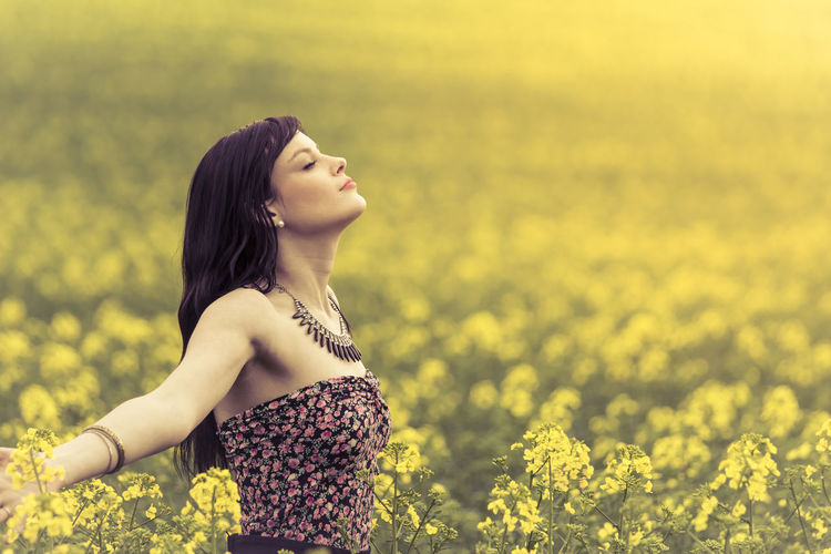 Happy positive woman in sunny summer ocean of yellow flowers. Attractive genuine young girl enjoying the warm summer sun in a wide green and yellow meadow. Copyspace in the right. Beautiful Carefree Copyspace Dream Eyes Closed  Feelings Free Freedom Girl Happiness Hot Love Meadow Nature Peace Person Power Spring Summer Sun Sunrise Sunset Woman Young Youth