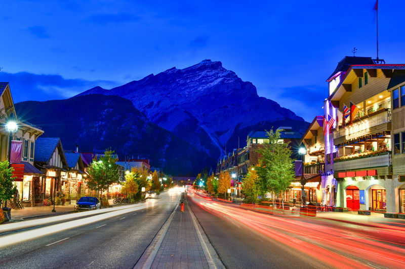 Street view of famous Banff Avenue at twilight time. Banff is a resort town and one of Canada's most popular tourist destinations. Illuminated Road Transportation Building Exterior Architecture Sky City Mountain Street Night Built Structure Motion Long Exposure Light Trail Nature Mode Of Transportation Mountain Range Blurred Motion Speed No People Outdoors Light Banff  Twilight Town Canada Avenue