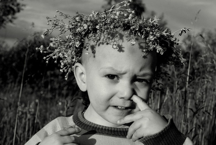 Portrait of boy wearing flower wreath while picking nose on field