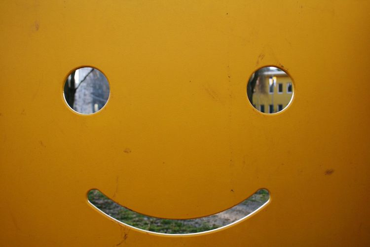 Close-up of yellow smiley face on yellow metal wall