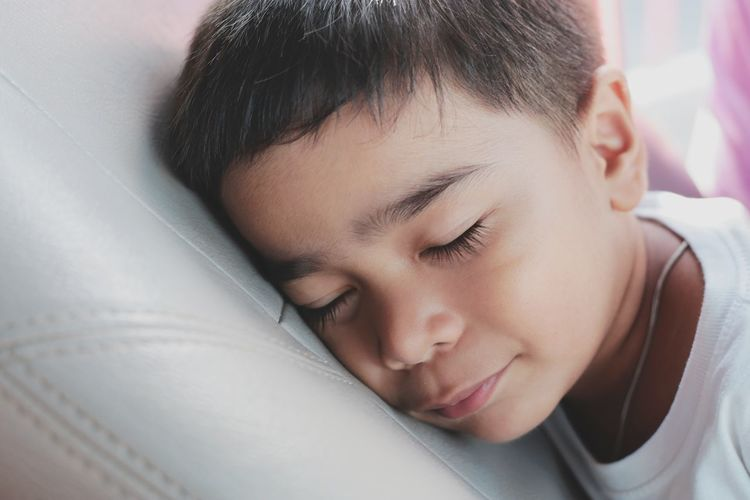 Close-up of cute boy sleeping on bed