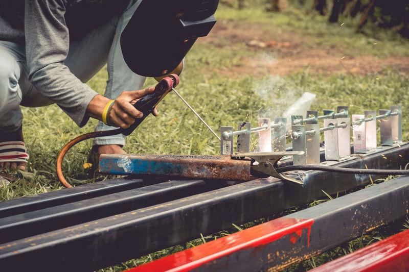 A welder holds welding rods and welding mask welds electricity pole. Industry Mechanic Welding Working Building Exterior Effort Engineering Engineers Fire Men Metal Occupation Repair Skill  Weld Welder Welding Mask Welding Rods Working