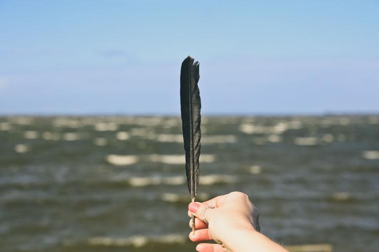 Close-up of hand holding umbrella against sea