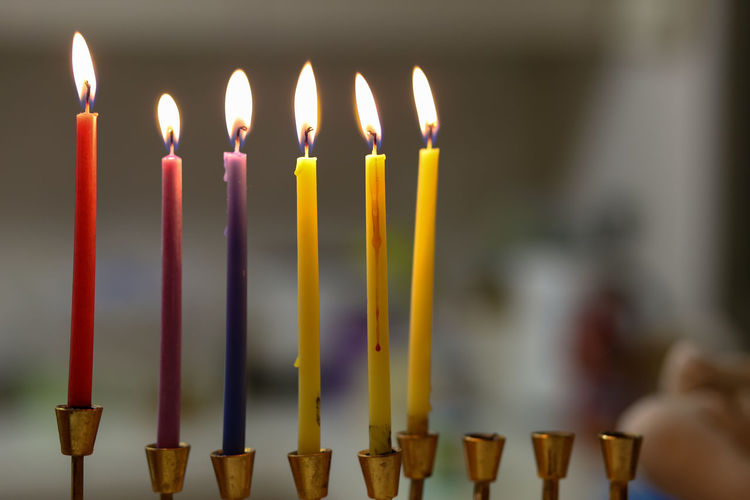 Close-up of colorful burning candles in church