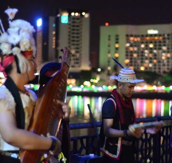 Sarawak street performers. Night life walks along the river. The performers wearing their cultural costume of Sarawak ethnic and playing a beautiful music. Cityoflight  Waterfrontcity Bytheriverside Kuchingcity Sarawakmalaysia Night Celebration Arts Culture And Entertainment Illuminated Men Event #urbanana: The Urban Playground Group Of People City Enjoyment Fun People Leisure Activity Performance