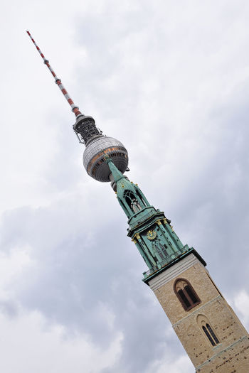 Low angle tilt view of St. Mary's Church(Marienkirche) over spire of Television Tower (Fernsehturm) in Berlin, Germany Been There. Church Diagonal Fernsehturm Berlin  St Mary's Church TV Tower Tilt Angle Architecture Building Exterior Built Structure City Cloud - Sky Day Discover Berlin Landmark Low Angle View Marienkirche No People Outdoors Sky Tall - High Television Tower Tower Travel Destinations