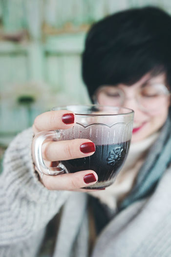 Close-up of mid adult woman drinking coffee at home