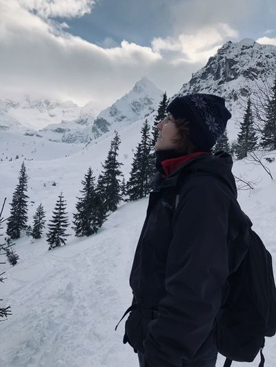 Woman standing on snowcapped mountains during winter